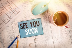 Text sign showing See You Soon. Conceptual photo used for saying goodbye to someone and going to meet again soon technological devices colored reminder paper office supplies keyboard mouse.