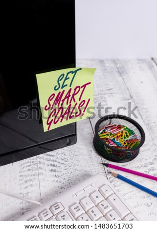 Text sign showing Set Smart Goals. Conceptual photo list to clarify your ideas focus efforts use time wisely Note paper taped to black computer screen near keyboard and stationary.