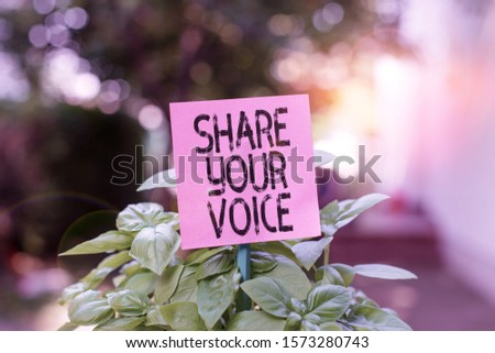 Text sign showing Share Your Voice. Conceptual photo asking employee or member to give his opinion or suggestion Plain empty paper attached to a stick and placed in the green leafy plants.