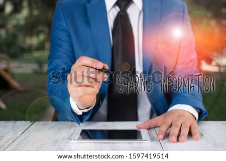 Text sign showing Sharing Information. Conceptual photo exchange of data between various organizations Businessman holds pen and points into copy space.