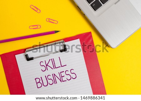 Text sign showing Skill Business. Conceptual photo Ability to handle business venture Intellectual expertise Slim metallic laptop clipboard paper sheet clips pencil colored background. #1469886341