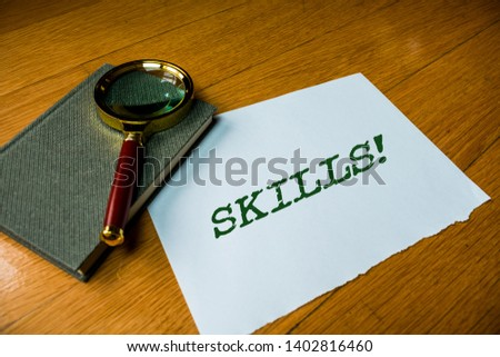 Text sign showing Skills. Conceptual photo ability do something very well by nature Close up electronic device gadget magnifying glass resting wooden table. #1402816460