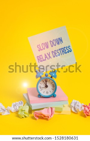 Text sign showing Slow Down Relax Destress. Conceptual photo calming bring happiness and put you in good mood Alarm clock sticky note paper balls stacked notepads colored background.