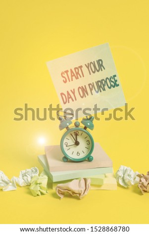 Text sign showing Start Your Day On Purpose. Conceptual photo Have clean ideas of what you are going to do Alarm clock sticky note paper balls stacked notepads colored background.