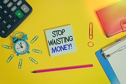 Text sign showing Stop Wasting Money. Conceptual photo advicing demonstrating or group to start saving and use it wisely Alarm clipboard calculator wallet clip band pencil notepad color background.