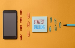 Text sign showing Strategy Building. Conceptual photo Leveraging Buying and acquiring others platforms Colored blank sticky note clips smartphone ballpoint trendy cool background.
