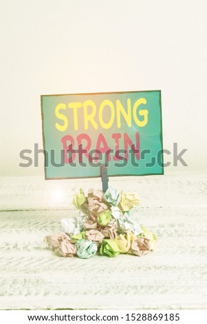 Text sign showing Strong Brain. Conceptual photo own firm attitudes and opinions and are not easily influenced Reminder pile colored crumpled paper clothespin reminder white wooden space.