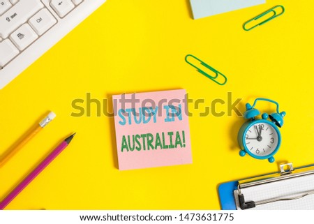 Text sign showing Study In Australia. Conceptual photo going into foreign country order complete your studies Flat lay above copy space on the white crumpled paper.