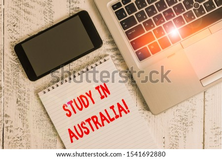 Text sign showing Study In Australia. Conceptual photo going into foreign country order complete your studies Metallic laptop blank ruled notepad smartphone lying old wooden table.