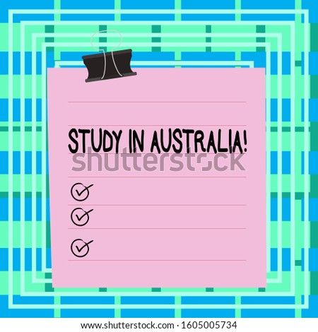 Text sign showing Study In Australia. Conceptual photo going into foreign country order complete your studies Paper lines binder clip cardboard blank square notebook color background.