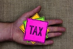 Text sign showing Tax. Conceptual photo Compulsory payment of taxes by people to government increase revenue Holding small pitches art papers thoughts ideas memories mat black shadow.