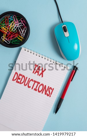 Text sign showing Tax Deductions. Conceptual photo reduction income that is able to be taxed of expenses Notebook and writing equipment with computer mouse above pastel backdrop. #1419979217