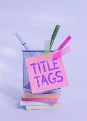 Text sign showing Title Tags. Conceptual photo the HTML element that specifies the title of a web page Sticky note arrow banners stacked pads metal pens holder pastel background.