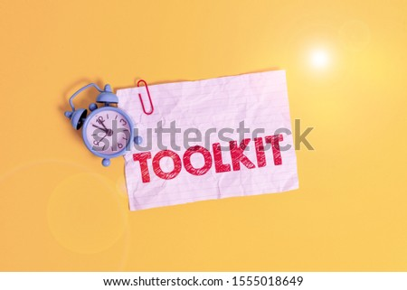 Text sign showing Toolkit. Conceptual photo set of tools kept in a bag or box and used for a particular purpose Metal alarm clock clip blank crushed note sheet colored background. #1555018649