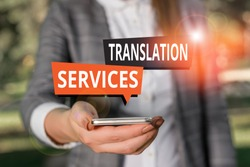 Text sign showing Translation Services. Conceptual photo organization that provide showing to translate speech Woman in grey suites holds mobile phone.