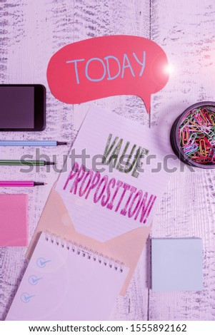 Text sign showing Value Proposition. Conceptual photo innovation service intended make product attractive Envelop speech bubble smartphone sheet pens spiral notepads clips wooden.