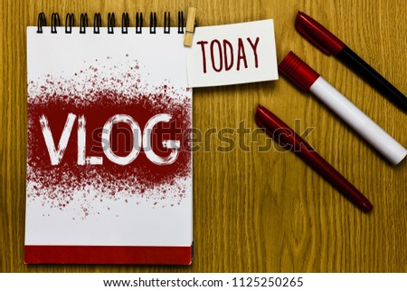 Text sign showing Vlog. Conceptual photo Entertaining multimedia self broadcasting news reporting stories Reminder appointment daily note paper work book job list marker pens clip.