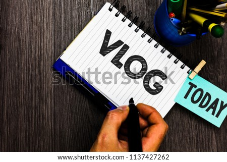 Text sign showing Vlog. Conceptual photo Entertaining multimedia self broadcasting news reporting stories Reminder appointment daily work pens penholder clip paperclip papers.