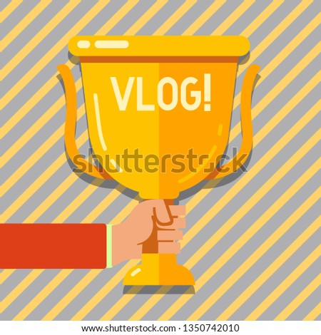 Text sign showing Vlog. Conceptual photo Entertaining multimedia self broadcasting news reporting stories Hand Holding Blank Golden Championship Winners Cup Trophy with Reflection.