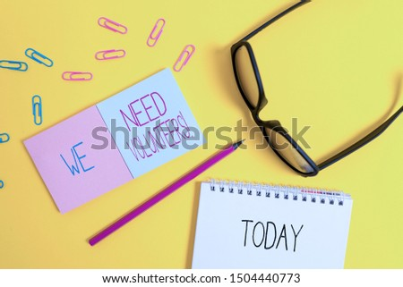 Text sign showing We Need Volunteers. Conceptual photo someone who does work without being paid for it Square blank sticky notepads pencil clips eyeglasses yolk color background.