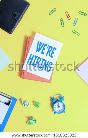 Text sign showing We Re Hiring. Conceptual photo Advertising Employment Workforce Placement New Job Pile of empty papers with copy space on the table.