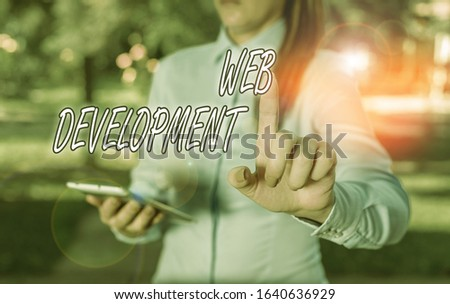 Text sign showing Web Development. Conceptual photo dealing with developing websites for hosting via intranet Woman in a blue business shirts pointing with her finger into empty space.
