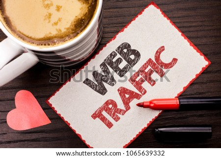 Text sign showing Web Traffic. Conceptual photo Internet Boost Visitors Audience Visits Customers Viewers written on Sticky Note on the wooden background Coffee Cup Heart Marker next to it. #1065639332