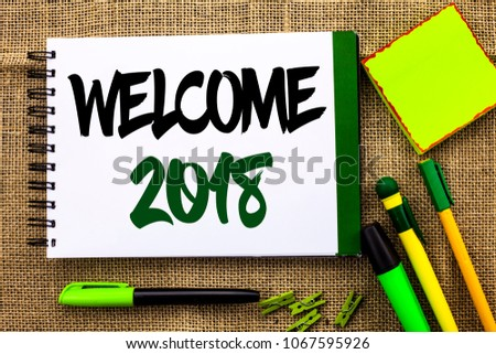 Text sign showing Welcome 2018. Conceptual photo Celebration New Celebrate Future Wishes Gratifying Wish written on Notebook Book on the jute background Pens Clips Sticky Note next to it. #1067595926