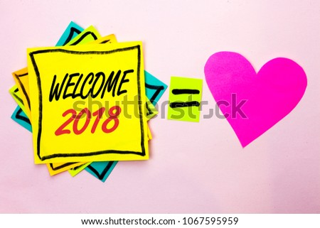 Text sign showing Welcome 2018. Conceptual photo Celebration New Celebrate Future Wishes Gratifying Wish written on Yellow Sticky Note Paper on the plain background Pink Heart next to it. #1067595959