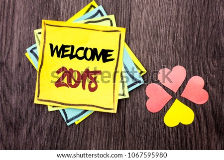 Text sign showing Welcome 2018. Conceptual photo Celebration New Celebrate Future Wishes Gratifying Wish written on Stacked Sticky Note Papers on the wooden background Hearts next to it. #1067595980