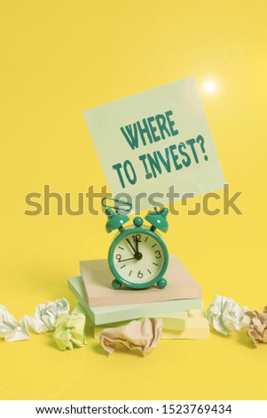 Text sign showing Where To Invest Question. Conceptual photo asking someone about place to put money into Alarm clock sticky note paper balls stacked notepads colored background.