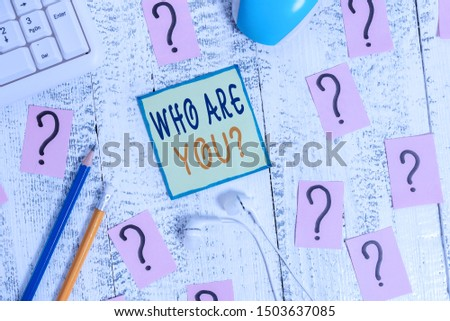 Text sign showing Who Are You question. Conceptual photo asking demonstrating identity or demonstratingal information Writing tools, computer stuff and scribbled paper on top of wooden table.