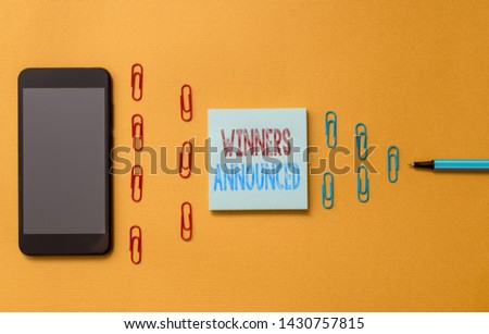 Text sign showing Winners Announced. Conceptual photo Announcing who won the contest or any competition Colored blank sticky note clips smartphone ballpoint trendy cool background.