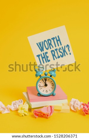 Text sign showing Worth The Risk Question. Conceptual photo asking if certain action balanced with its reaction Alarm clock sticky note paper balls stacked notepads colored background.