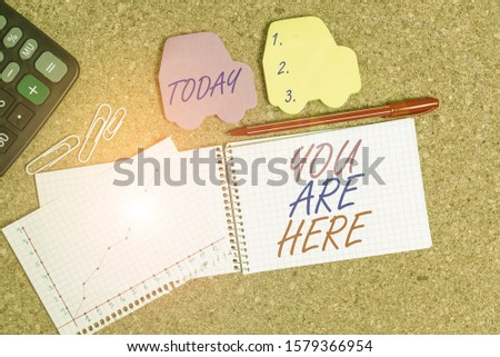 Text sign showing You Are Here. Conceptual photo This is your location reference point global positioning system Desk notebook paper office cardboard paperboard study supplies table chart. #1579366954