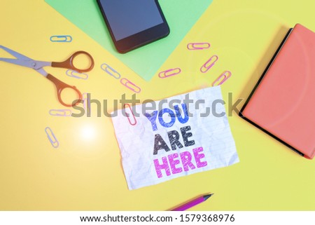 Text sign showing You Are Here. Conceptual photo This is your location reference point global positioning system Paper sheets pencil clips smartphone scissors notebook colored background. #1579368976