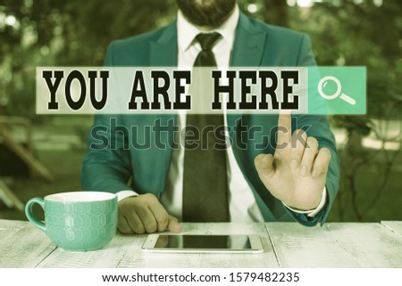 Text sign showing You Are Here. Conceptual photo This is your location reference point global positioning system Businessman with pointing finger in front of him. #1579482235
