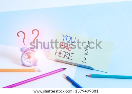 Text sign showing You Are Here. Conceptual photo This is your location reference point global positioning system Mini size alarm clock beside stationary placed tilted on pastel backdrop. #1579499881