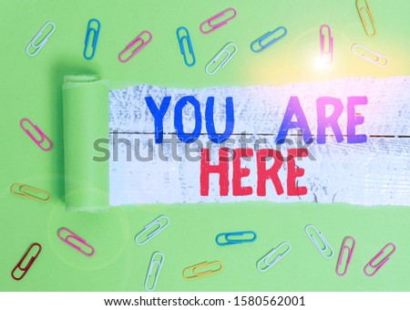 Text sign showing You Are Here. Conceptual photo This is your location reference point global positioning system Paper clip and torn cardboard placed above a wooden classic table backdrop. #1580562001