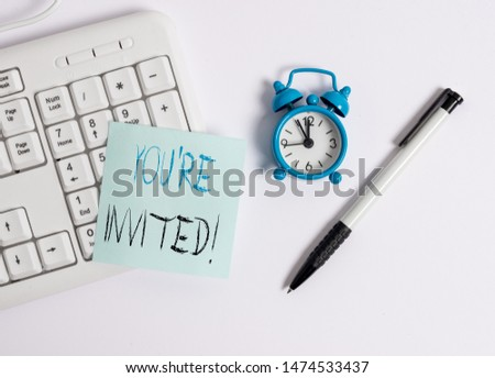 Text sign showing You Re Invited. Conceptual photo make a polite friendly request to someone go somewhere White pc keyboard with empty note paper above white background. #1474533437