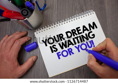 Text sign showing Your Dream Is Waiting For You. Conceptual photo Goal Objective Intention Target Yearning Plan Man hold holding blue marker notebook page markers table messages ideas. #1126714487