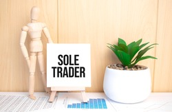 text sole trader on easel with office tools and paper.Top view.