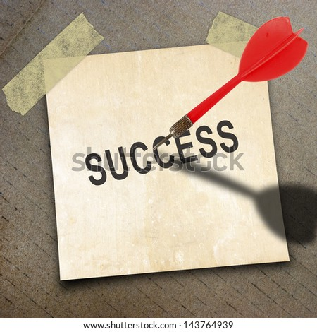 text success on short note paper and red dart on the packing paper box texture background