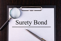 Text SURETY BOND is written on a notebook with a pen and a magnifying glass lying on the table. Business concept.