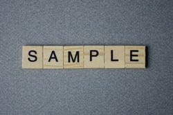 text the word sample from brown wooden small letters with black font on an gray table