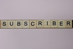 text the word subscriber from gray wooden small letters with black font on an pink table