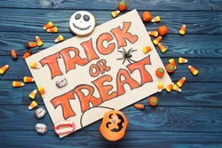Text Trick or Treat with halloween candies on wooden background