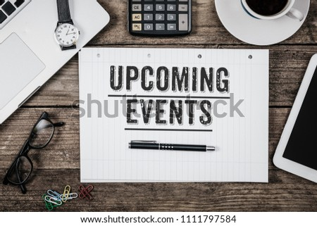 Text Upcoming Events written in notepad, Office desk with electronic devices, computer and paper, wood table from above, concept image for blog title or header image. Aged vintage color look. #1111797584
