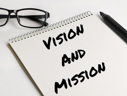 Text VISION AND MISSION on notebook with marker pen and eye glasses.Business concept.