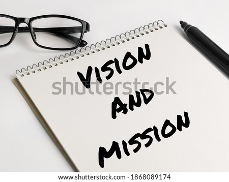 Text VISION AND MISSION on notebook with marker pen and eye glasses.Business concept. Photo stock ©